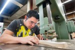 A young man works on a project in a woodworking shop.