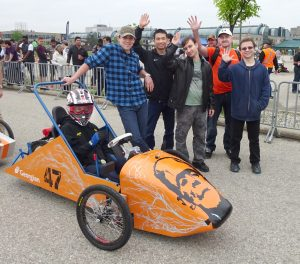 group of five men waving while standing next to orange electric vehicle outside