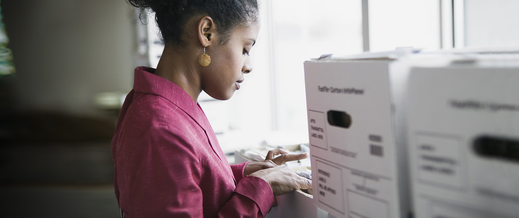 A woman in a pink blazer sorting through legal documents