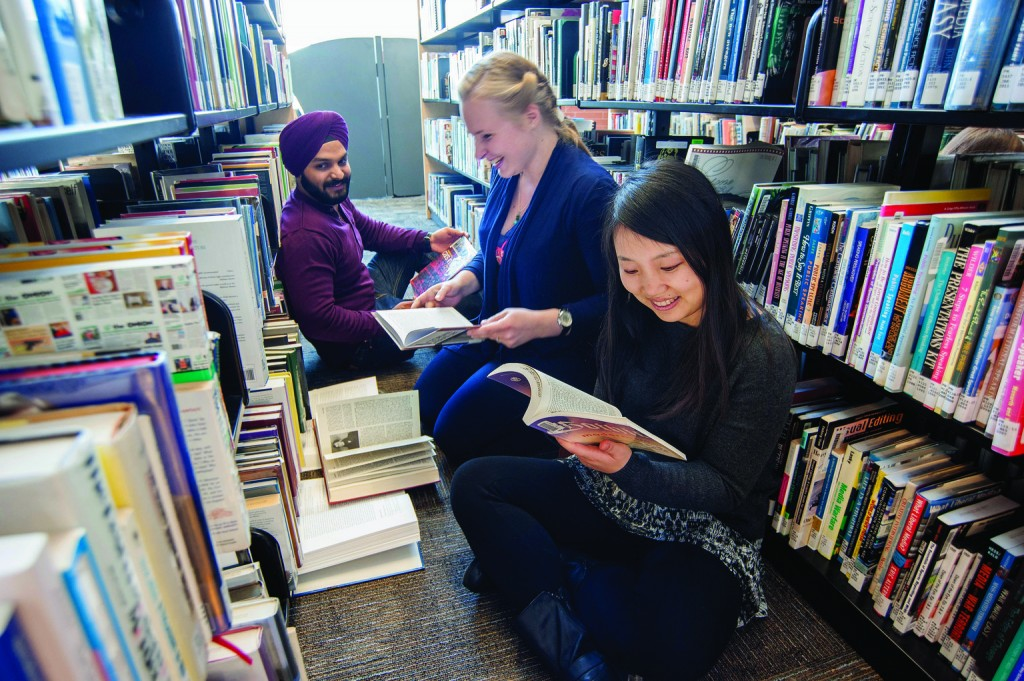 3 Georgian College students reading library books
