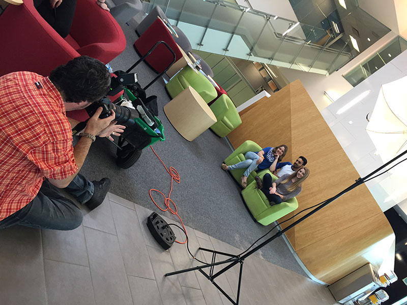 a photographer sitting on the floor taking photos of three students sitting on a green couch