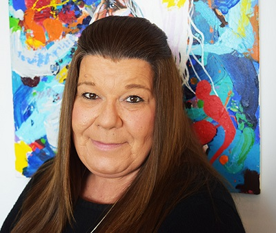 Female Indigenous Studies professor; head shot, standing in front of Indigenous art