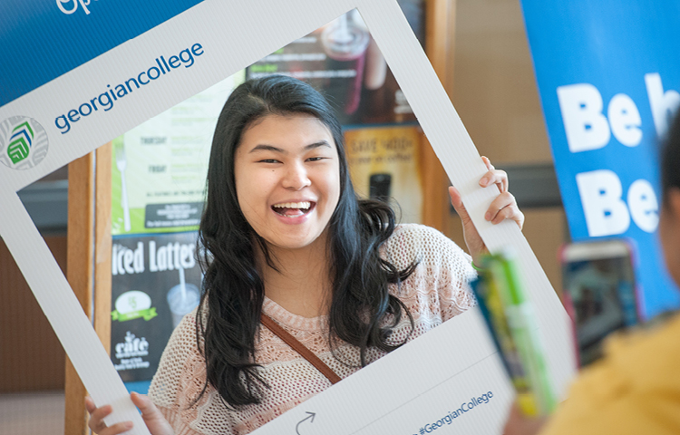 A smiling prospective student smiles poses with a mocked up full size cardboard cutout of a social media photo