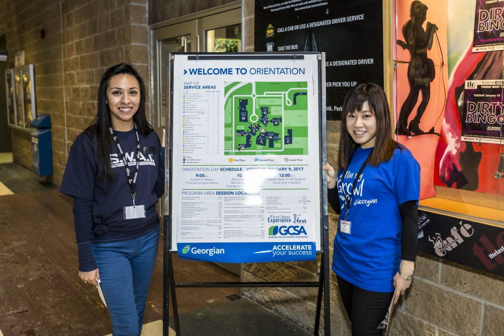 two female students volunteering at Orientation Day and welcoming new students to Georgian