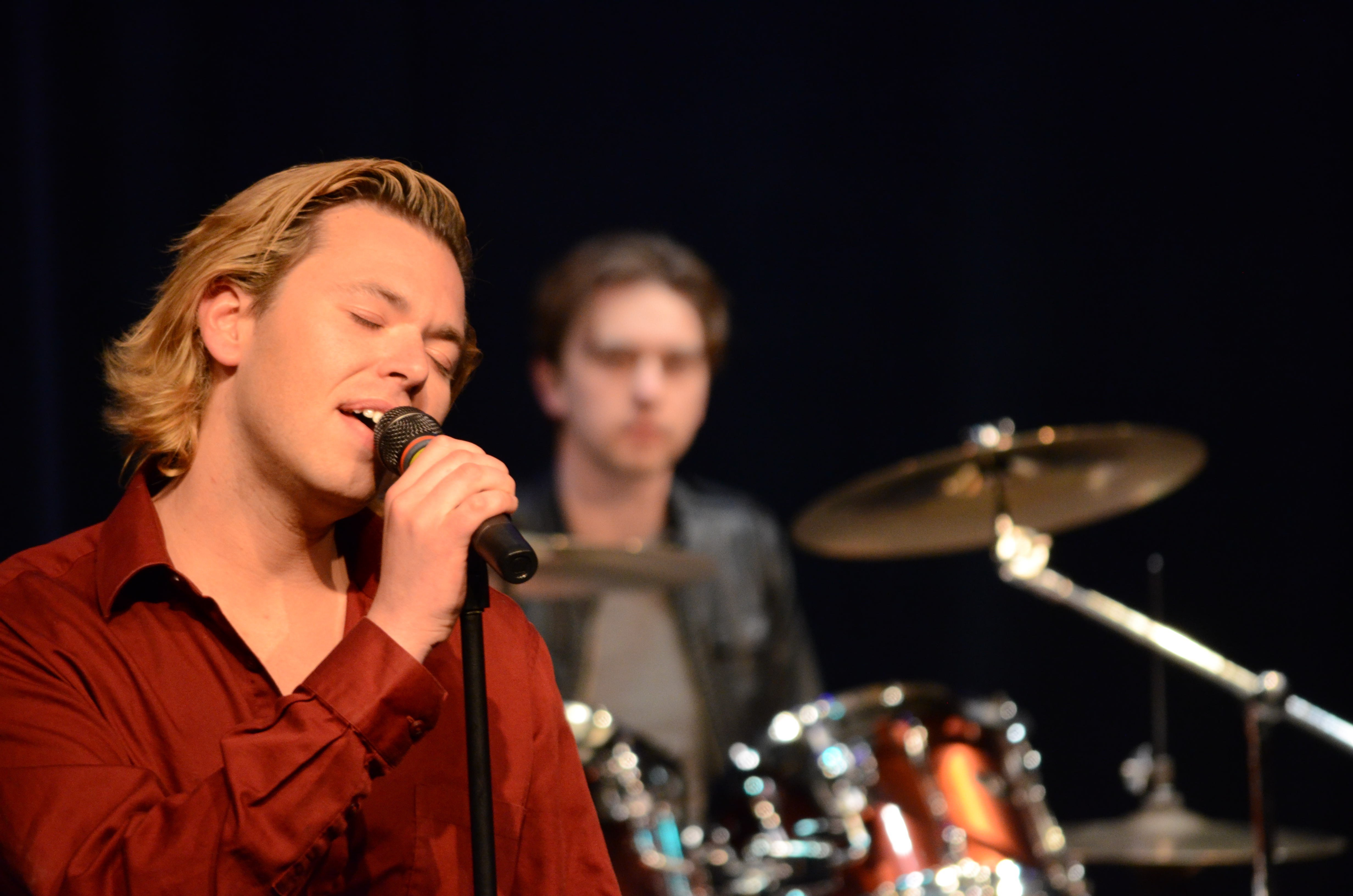 a young man with blond hair wearing a red shirt singing into a microphone with a guy playing drums in the background