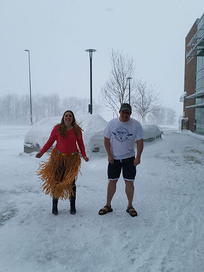 A girl wearing a grass skirt and a guy in shorts and t-shirt stand on a snowy sidewalk.