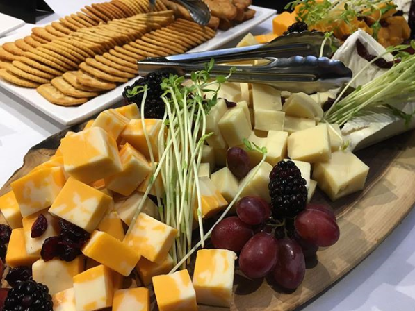 Assorted cheese, crackers, and grapes on a live-edge wooden board