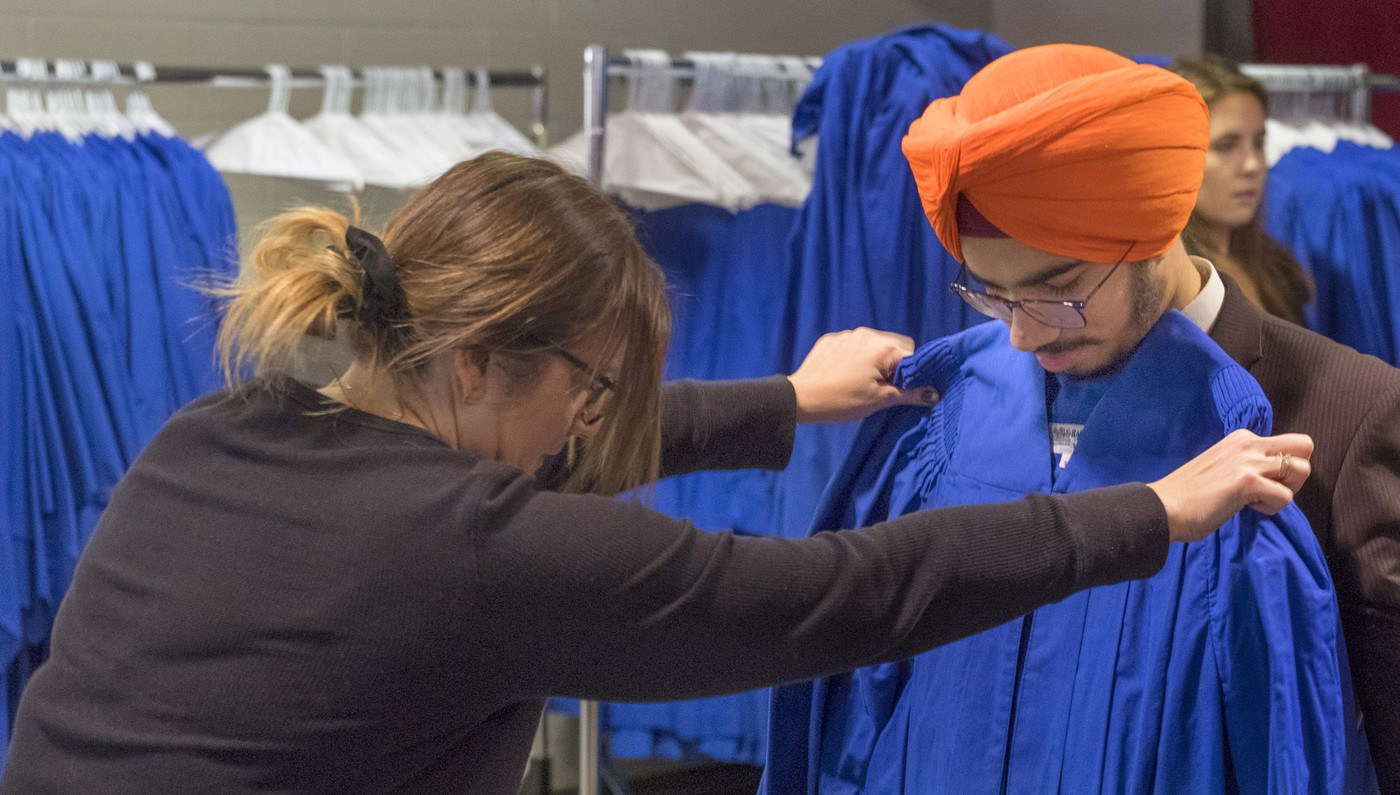 A college staff holds a convocation gown up against a student to check for sizing