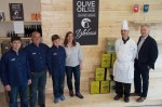 A group of people including one in chef's whites stand in front of an olive oil display.