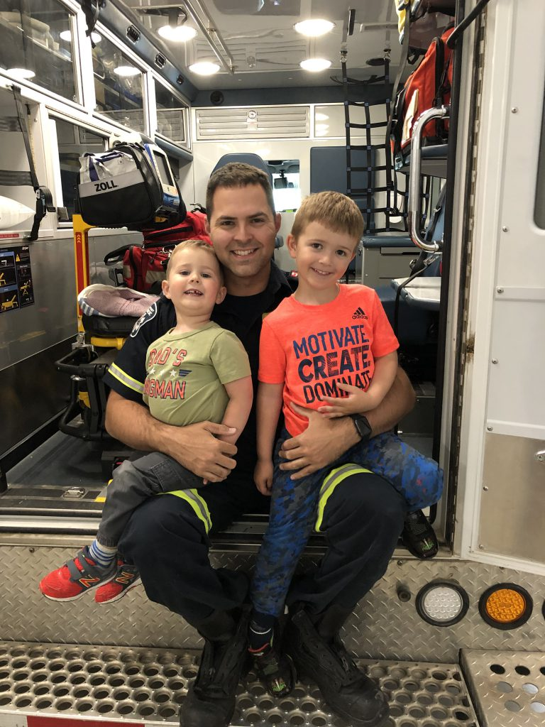 A person with brown hair and dressed in a paramedic uniform sits in the back of an ambulance with two children on their lap, all of them smiling at the camera.