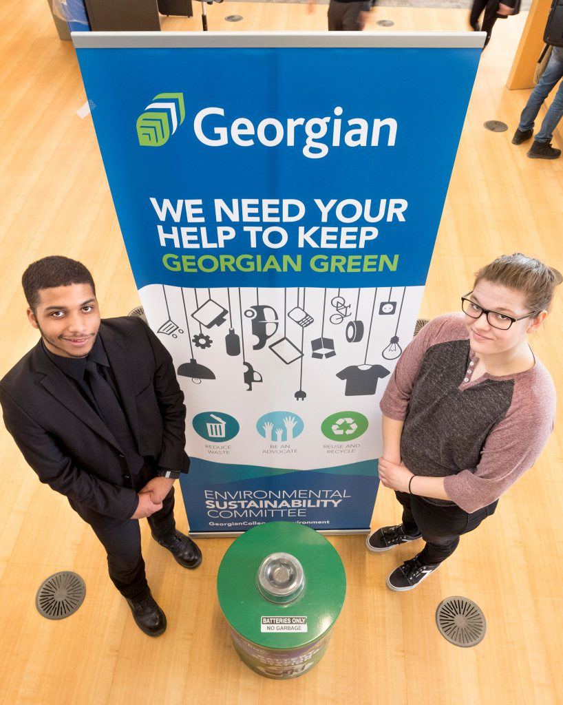 "A male student with dark hair, slight mustache wearing a black suit standing beside a pull-up banner with the Georgian logo and ""WE NEED YOUR HELP TO KEEP GEORGIAN CLEAN."" A blonde female student with glasses wearing a brown shirt, and pink sweater is standing on the other side of the banner."