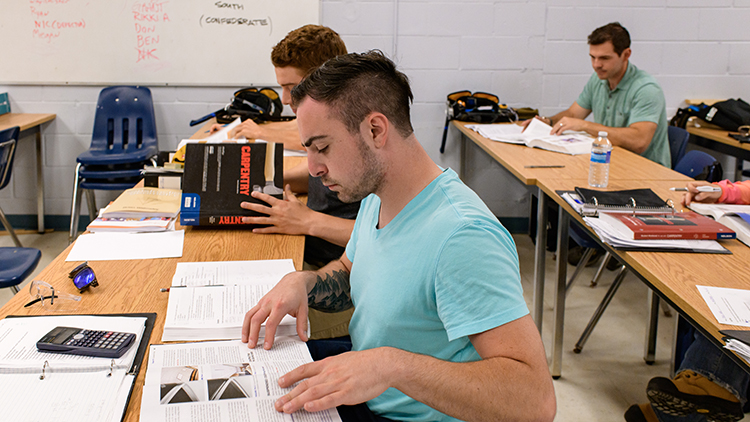 Georgian-Muskoka-construction-trades-pre-apprenticeship-students-flip-through-pages-of-textbook-in-classroom