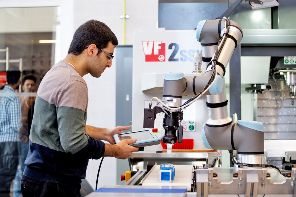 A male with dark hair and glasses working on a robotics machine