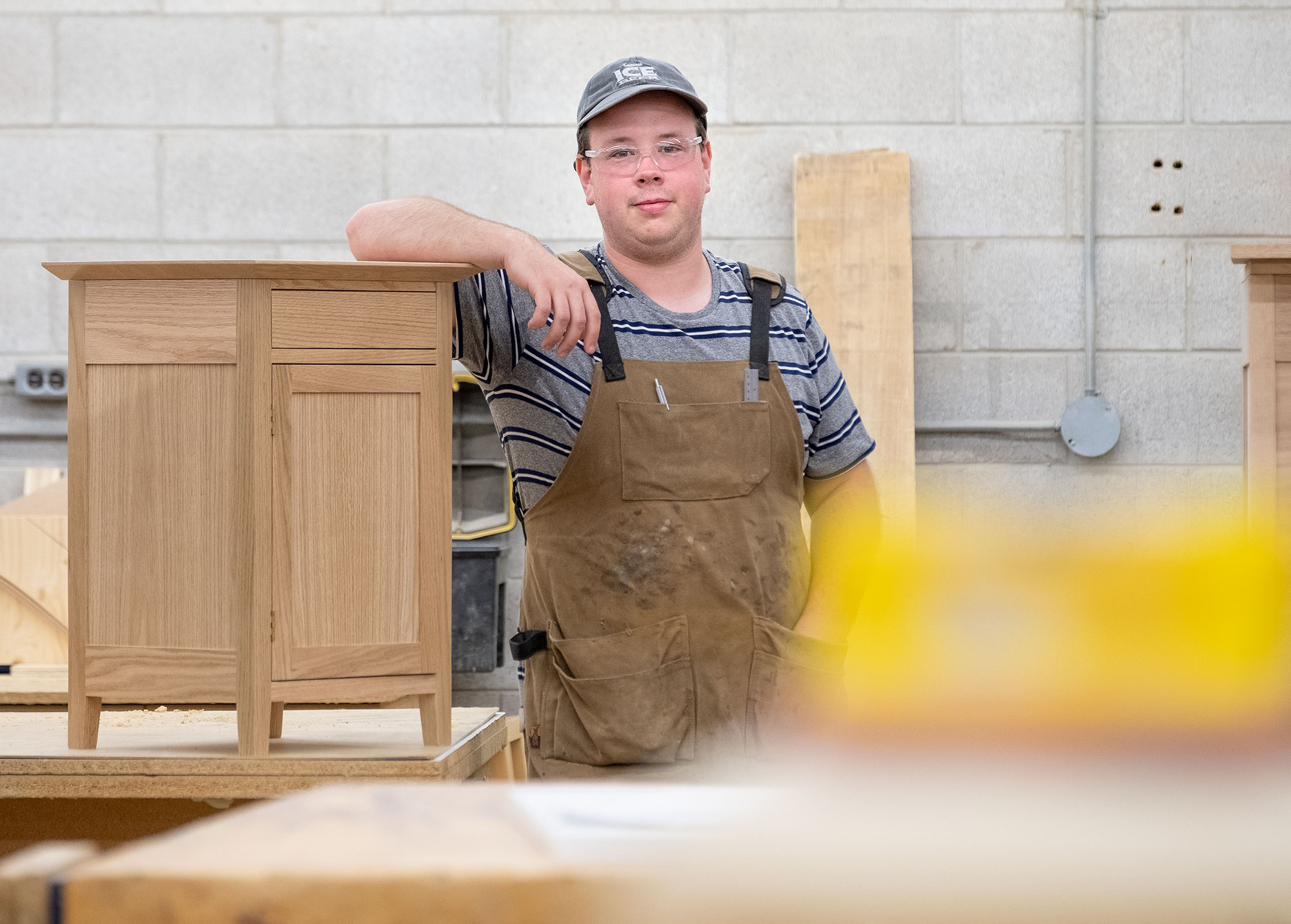 A white male wearing overalls leaning on a cabinet. He's wearing ia blue baseball hat and a blue and white striped shirt.