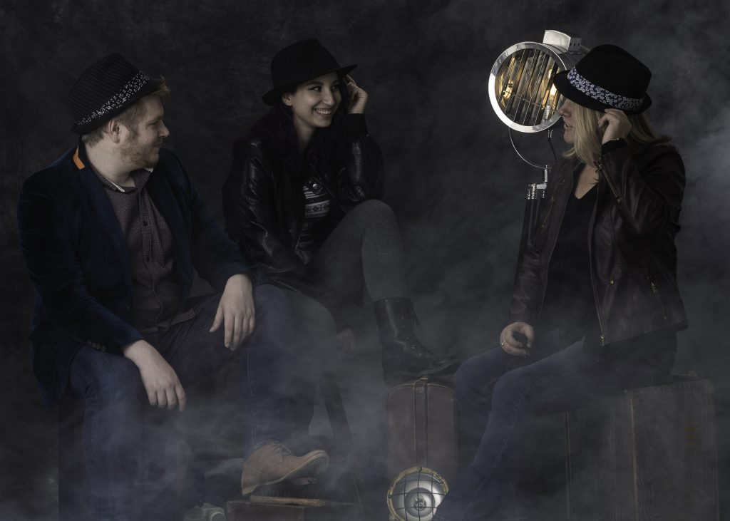 Joseph Smith, Emma Morrone and Kim Annand sit on suitcases, dressed in denim, leather jackets and fedora hats, on a photo shoot set for The Giving Portrait