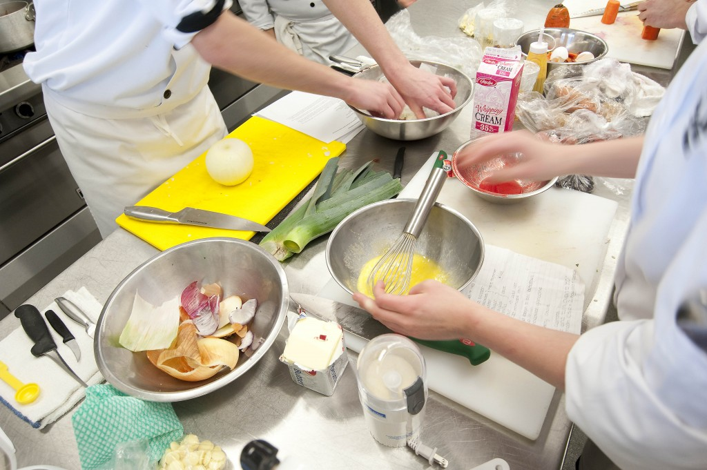 Busy hands are shown working in a culinary lab.