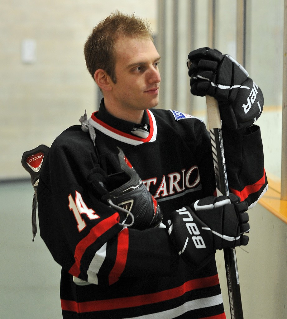 Anthony, wearing his hockey gear and holding a hockey stick