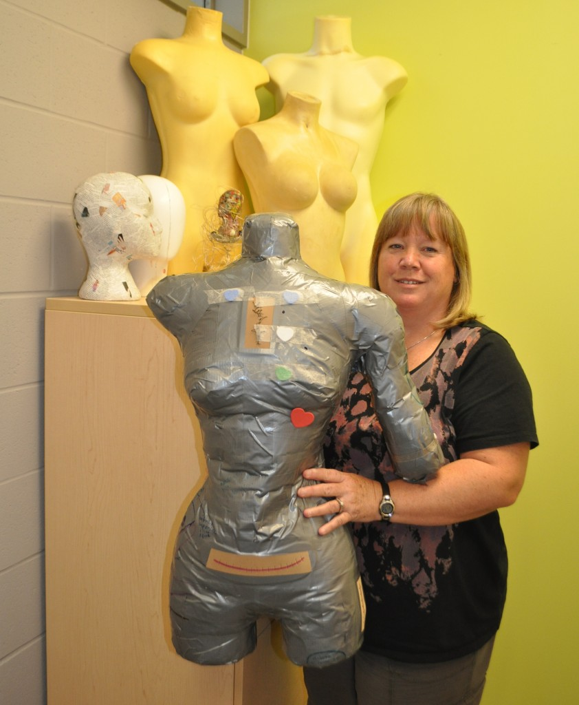 Yvonne stands next to a life-sized duct tape torso