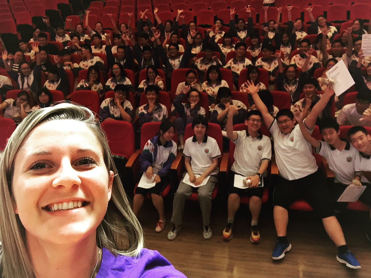 Melissa standing on a stage, taking a selfie, with school kids behind her, at a school in China