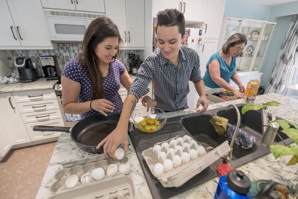 Two women cracking eggs into a mixing bowl, while another woman stands behind them getting a kitchen utensil out of a drawer
