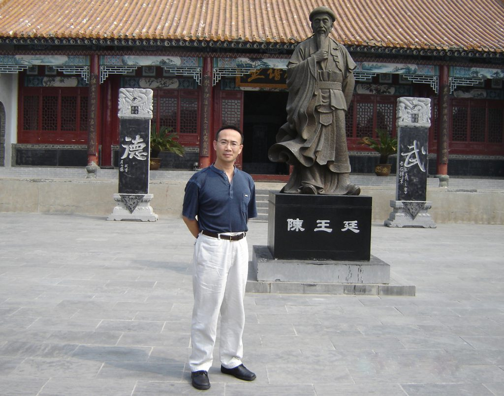 Person stands outside in front of a statue and building and looks at the camera.