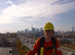 A young girl wears safety clothing, including yellow helmet, posing with Toronto skyline in the background.