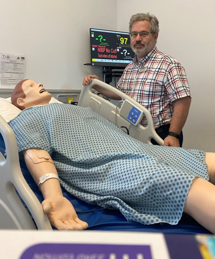 A person smiles at the camera while standing next to a patient simulator in a hospital bed.