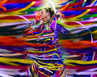 A dancer, mid-movement, in colourful traditional first nations clothing