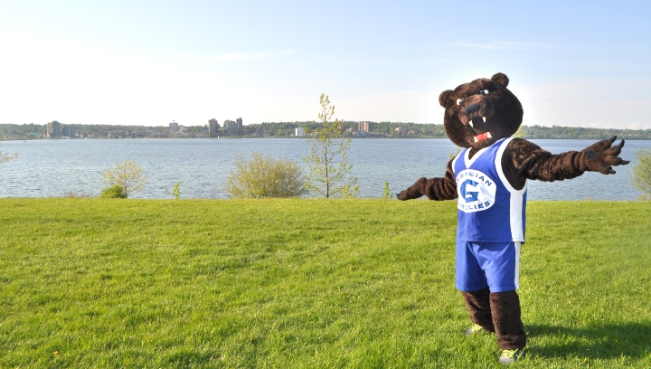 Growler mascot standing in front of Lake Simcoe
