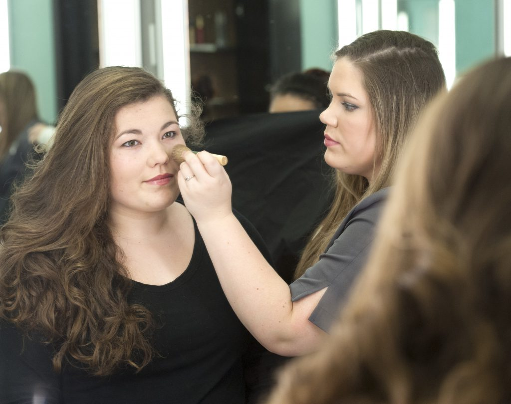 Student applying makeup to a young woman