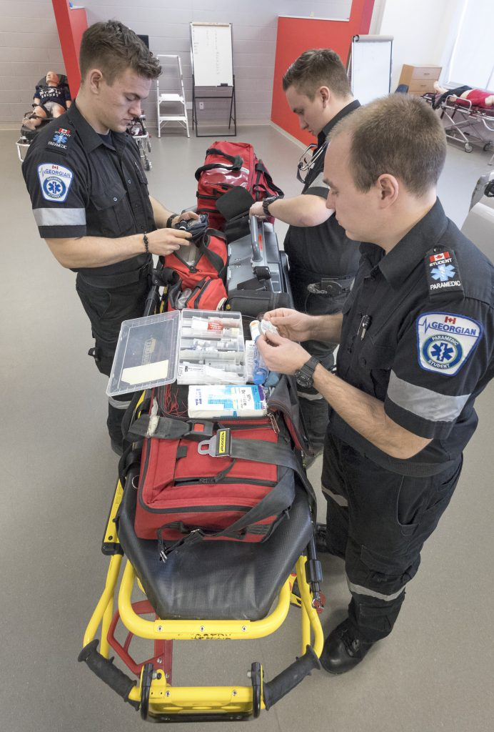 3 male paramedic students in the paramedic lab with stretcher and tools