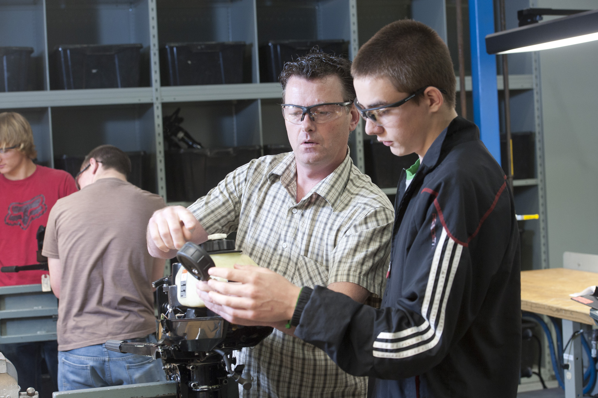 Professor in shop showing male student a part
