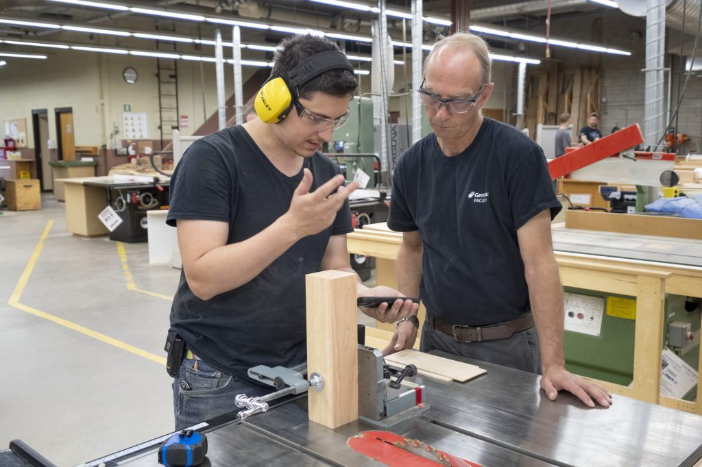 Male student and teacher working on a wood project in the shop