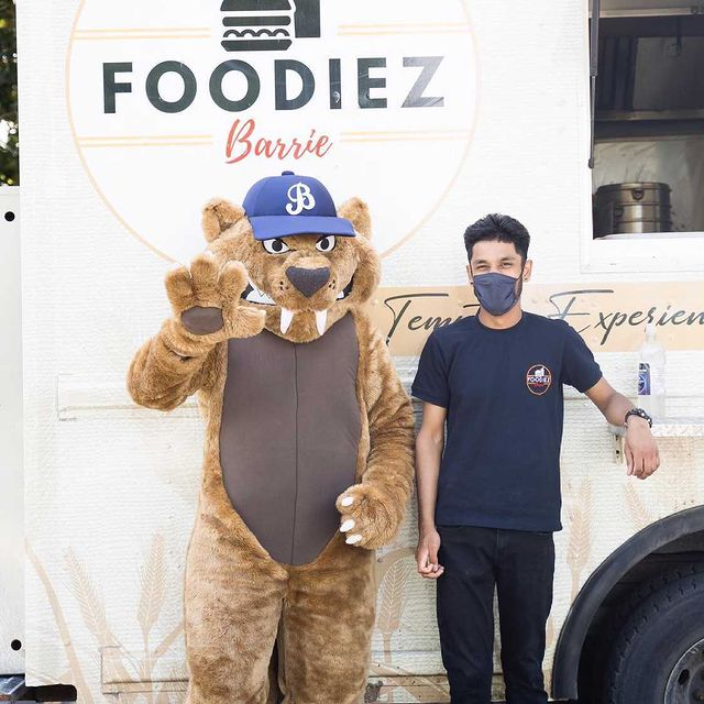 """A person with short, brown hair and wearing blank pants and a navy T-shirt and face mask stands next to a cat mascot wearing a blue cap with the letter """"B"""" on it, in front of a food truck that says Foodiez Barrie."""