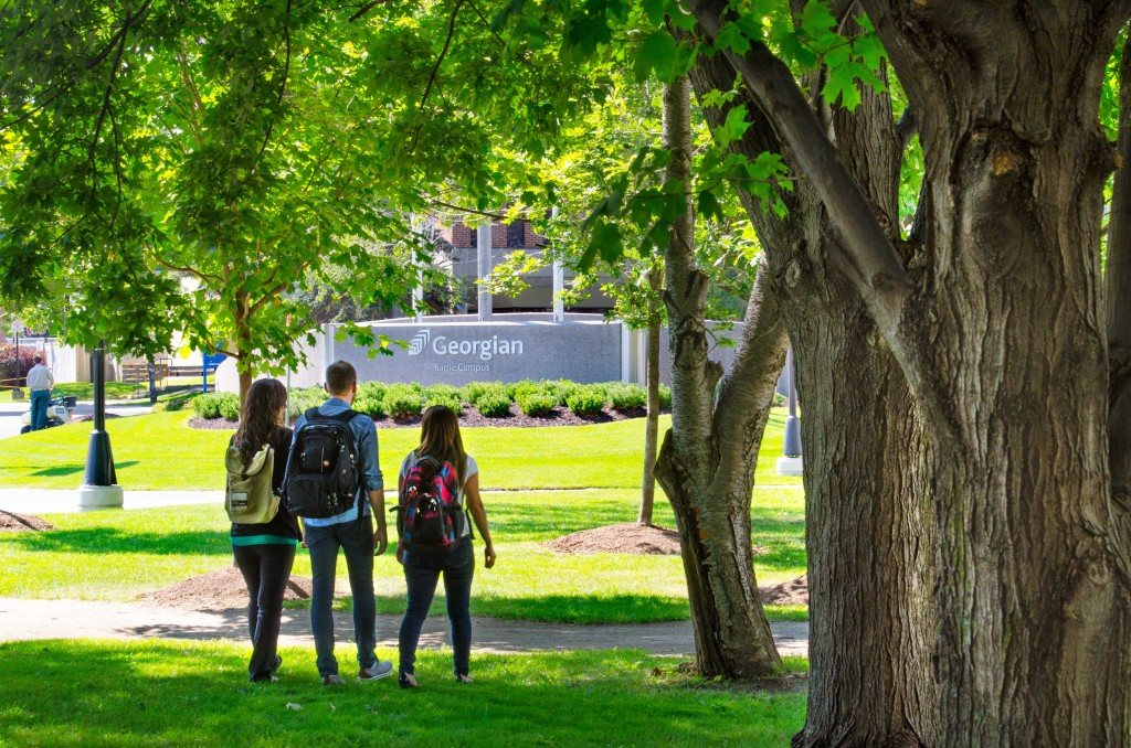 Three students walking through the courtyard of the Barrie Campus