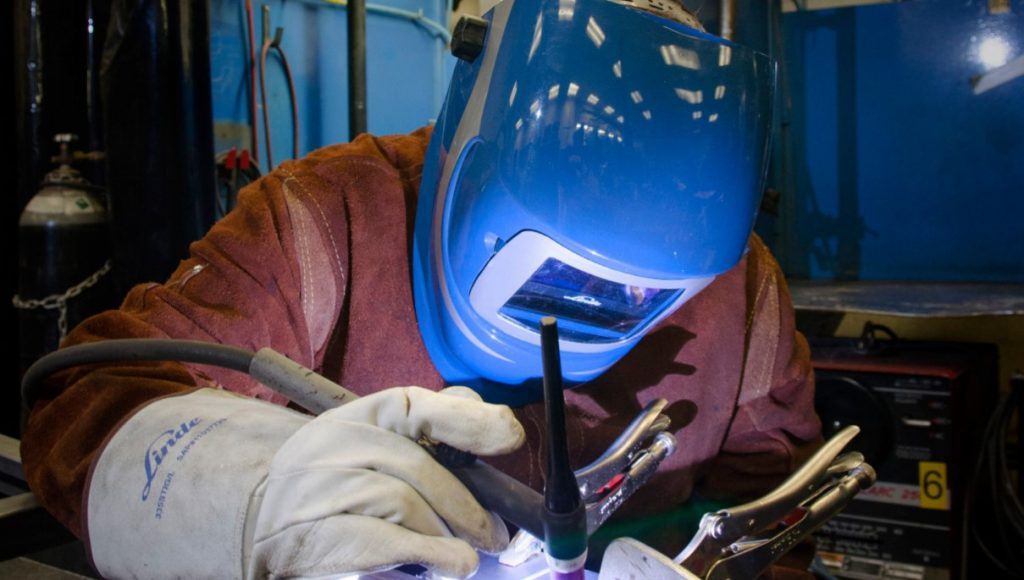 Student welding with mask on