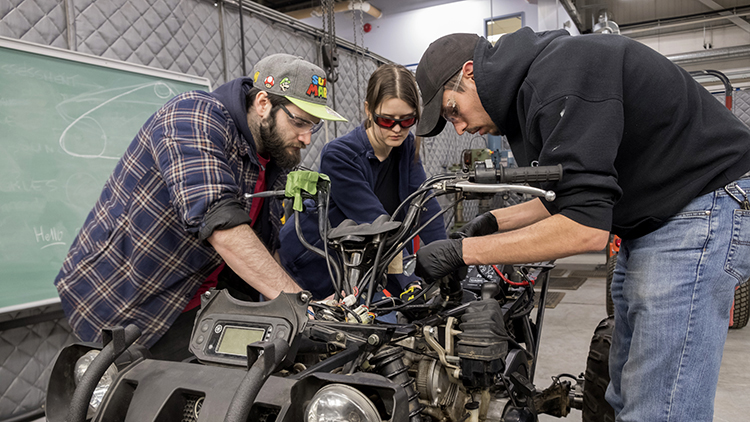 Two-male-and-one-female-student-work-on-an-ATV-in-the-Skilled-Trades-Centre