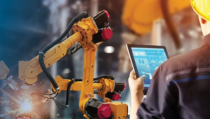 A person in a manufacturing plant, holding a tablet, standing in front of a robotic arm