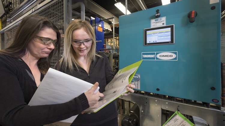 two female students wearing safety goggles and reading a binder in skilled trades lab
