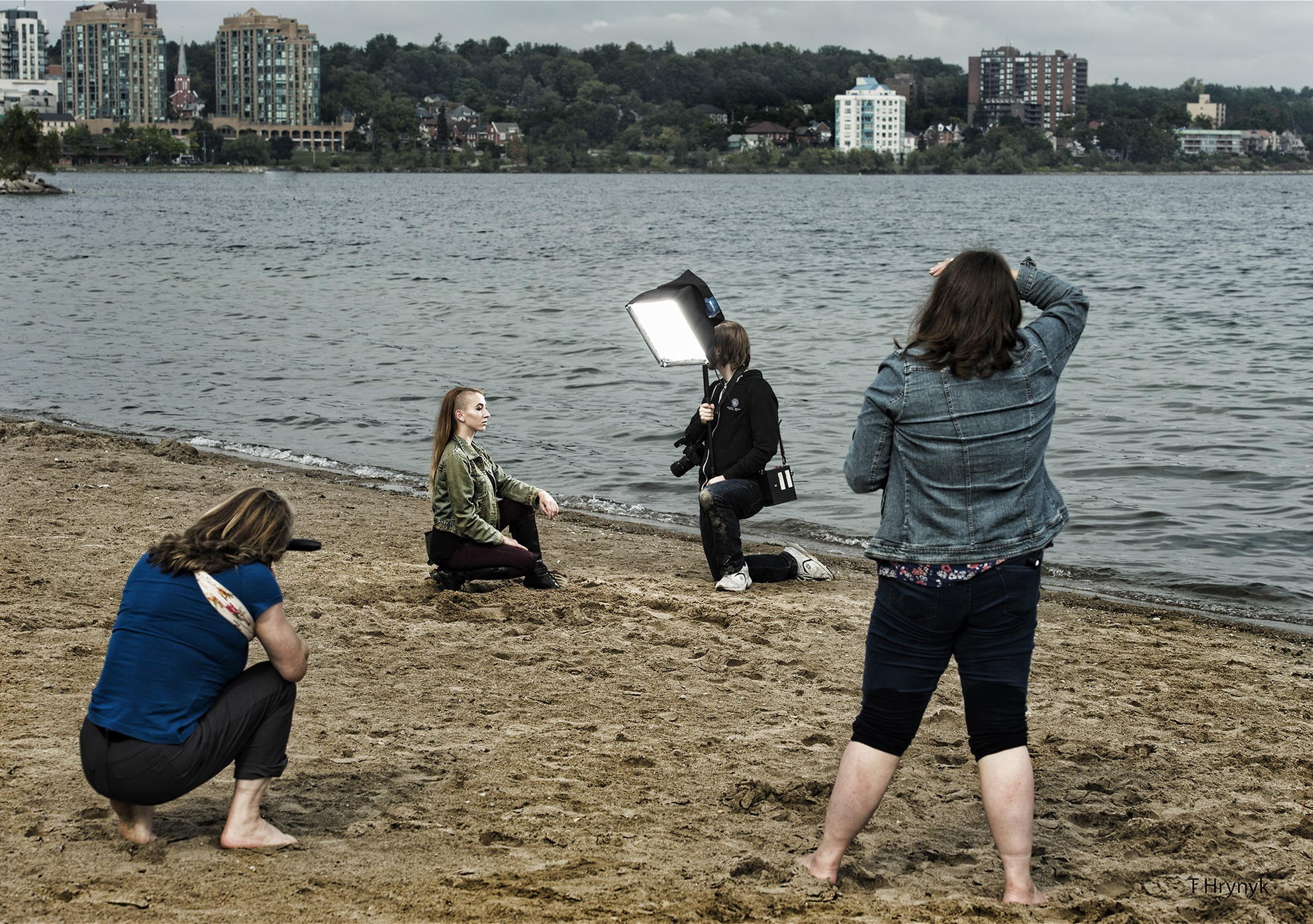 A female kneeling and posing on a beach in front of two female photographers and another female holding softbox lighting equipment