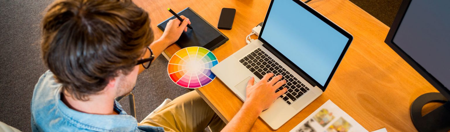 Art and Design Fundamentals student sitting at a desk using a laptop and colour wheel while drawing on a tablet with a stylus