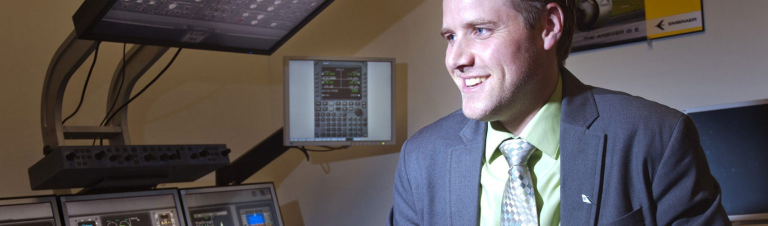 Aviation industry professional wearing a suit and tie while smiling next to flight simulator equipment