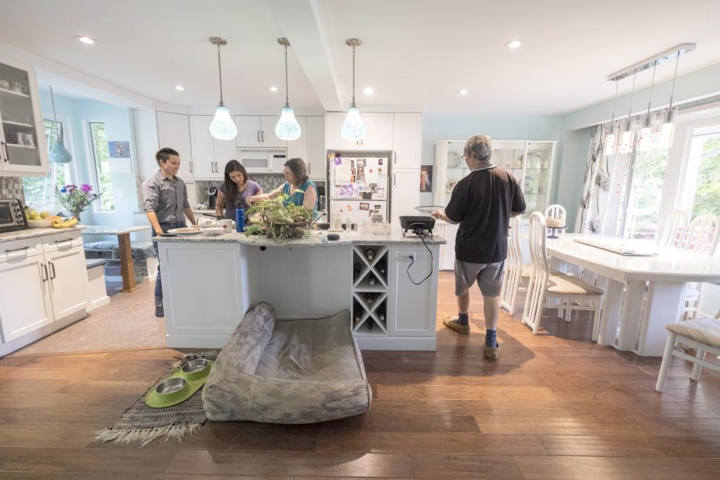 Four people in a big, bright open concept kitchen