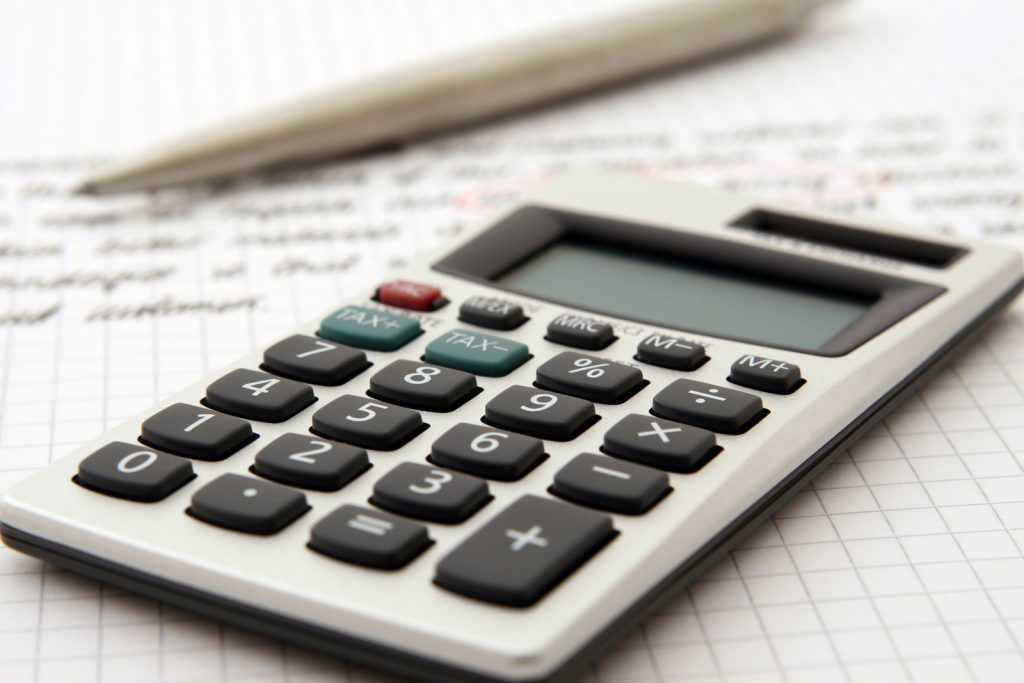 A calculator sits on a piece of a paper next to a pencil.