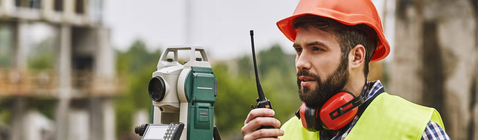 Civil Engineering Technician in a plaid shirt, safety vest and hard hat using a handheld transceiver and surveyor equipment