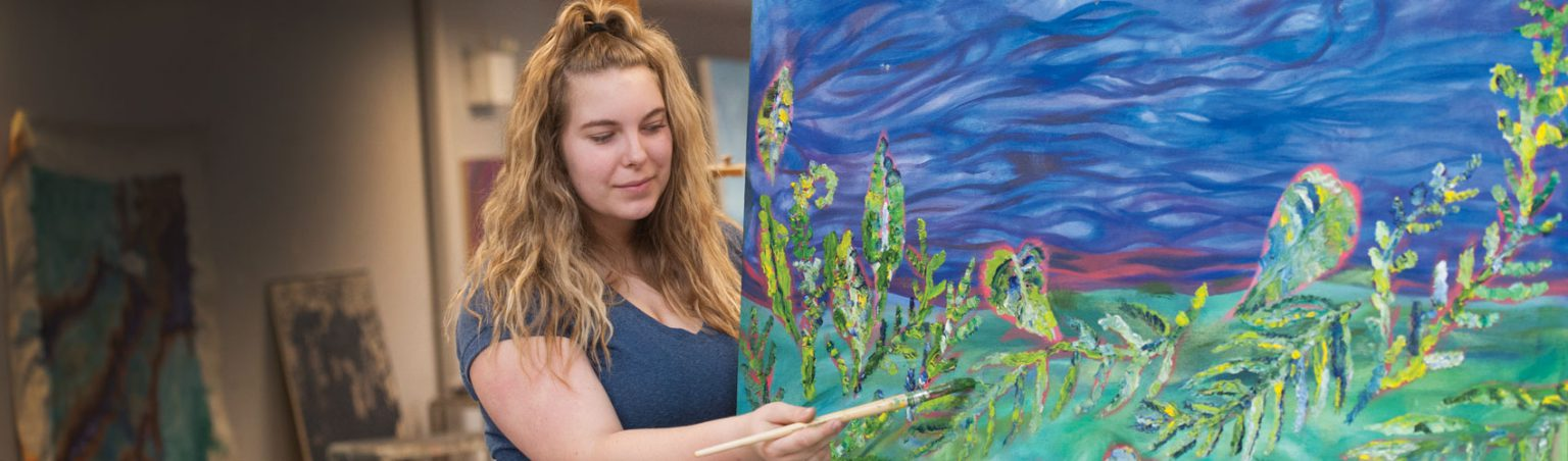 Fine Arts student with long, blonde hair holding a paint brush while painting plants, leaves and greenery on a large canvas