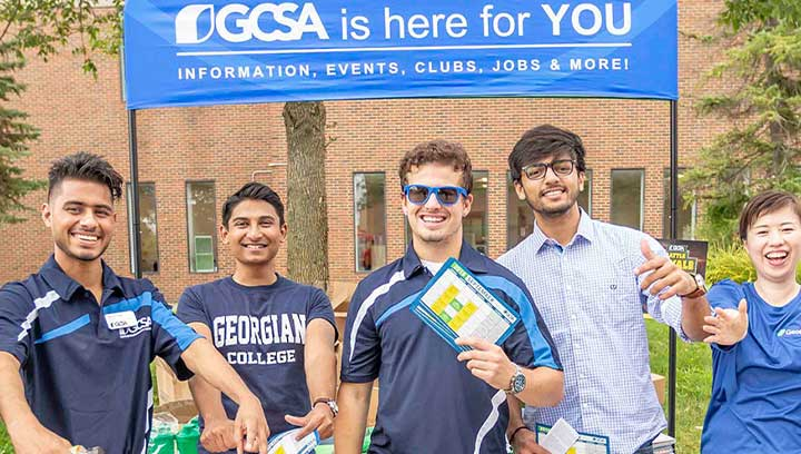 A group of students standing in front of a blue banner that reads: GCSA is here for you. Information, events, clubs, jobs and more!