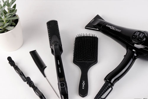 Black hairdressing tools on a white background with succulent in the background