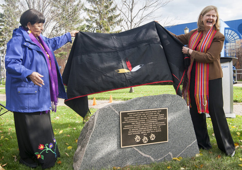 Elder Lorraine McRae and President and CEO MaryLynn West-Moynes unveil the Land Acknowledgment plaque on a stone outside at the Barrie Campus