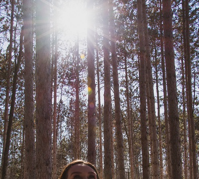 Woman's face in bottom portion of screen looking to sky with trees and sun peeking through them
